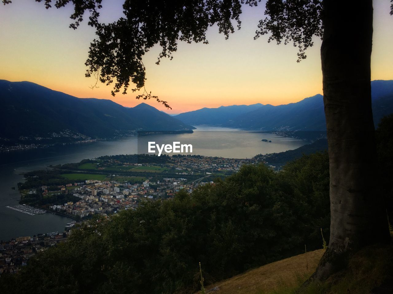 mountain, mountain range, tree, sunset, nature, scenics, water, sky, beauty in nature, no people, outdoors, tranquility, landscape, architecture, built structure, sea, growth, city, cityscape, building exterior, day