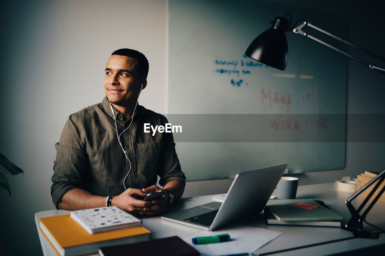 office, technology, one person, table, wireless technology, indoors, sitting, communication, computer, business, occupation, front view, young men, business person, businessman, real people, men, working, waist up, males, using laptop, new business
