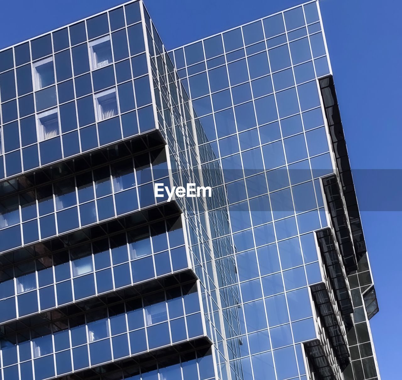 LOW ANGLE VIEW OF BLUE SKY AND MODERN OFFICE BUILDING AGAINST CLEAR BACKGROUND