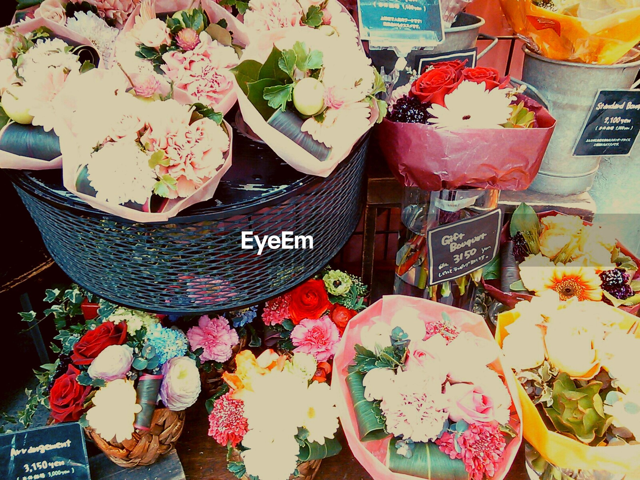 indoors, flower, freshness, variation, bouquet, multi colored, table, high angle view, choice, retail, for sale, decoration, food, food and drink, abundance, arrangement, vase, large group of objects, market stall
