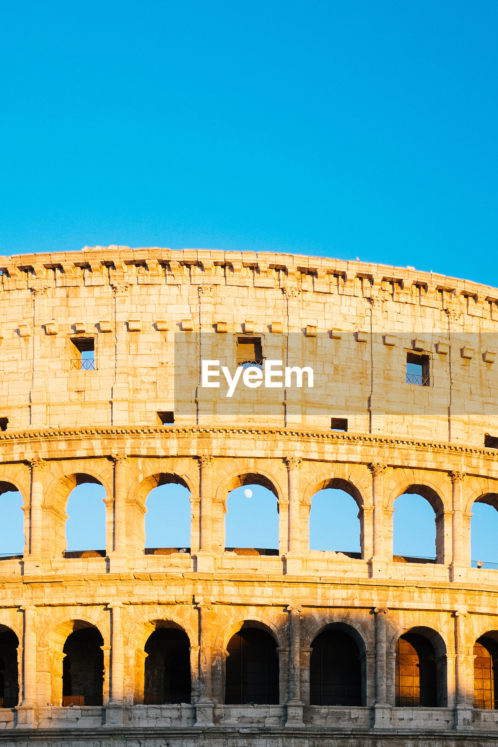 Low angle view of coliseum against clear blue sky on sunny day