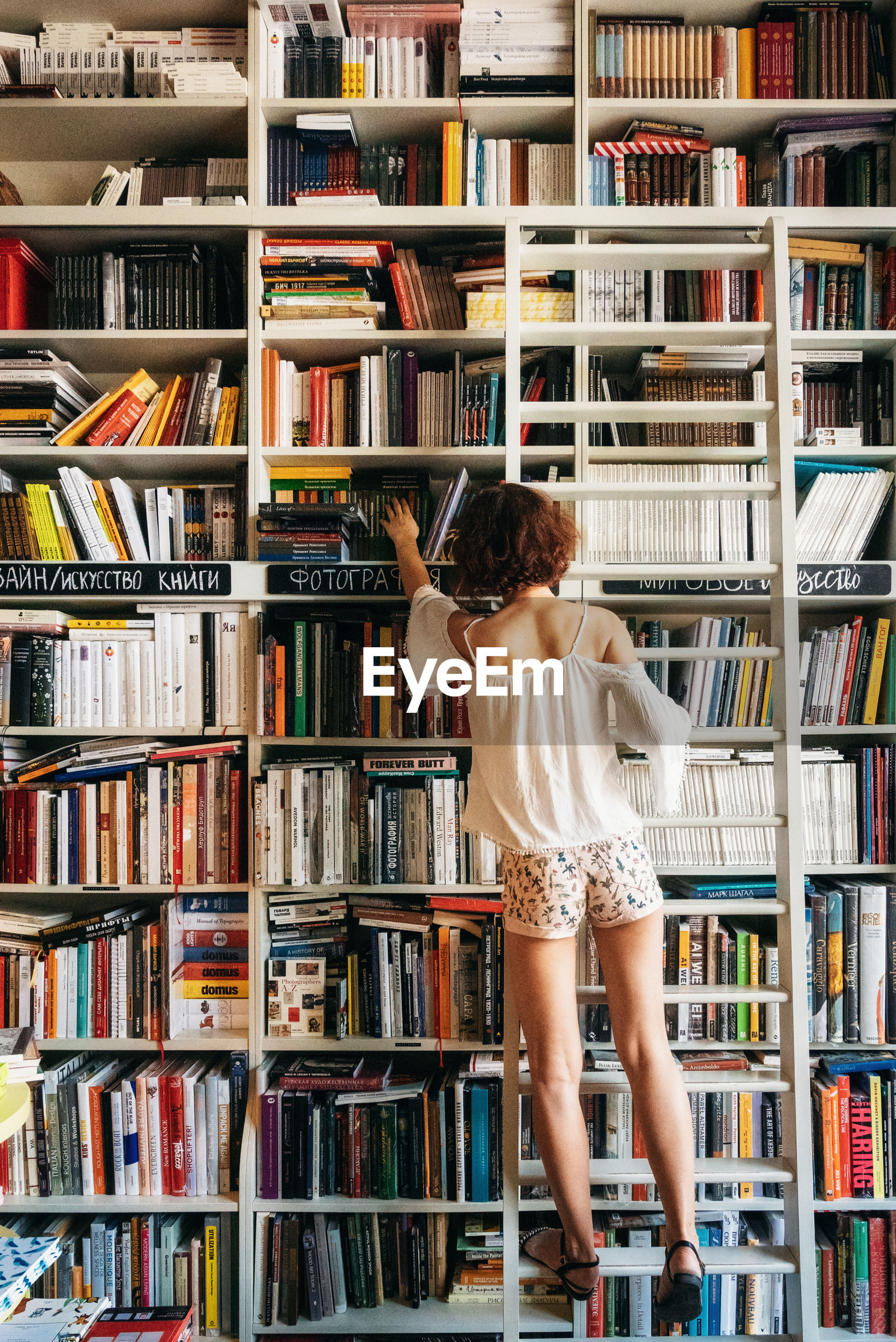 Full length rear view of woman taking books from shelves in library
