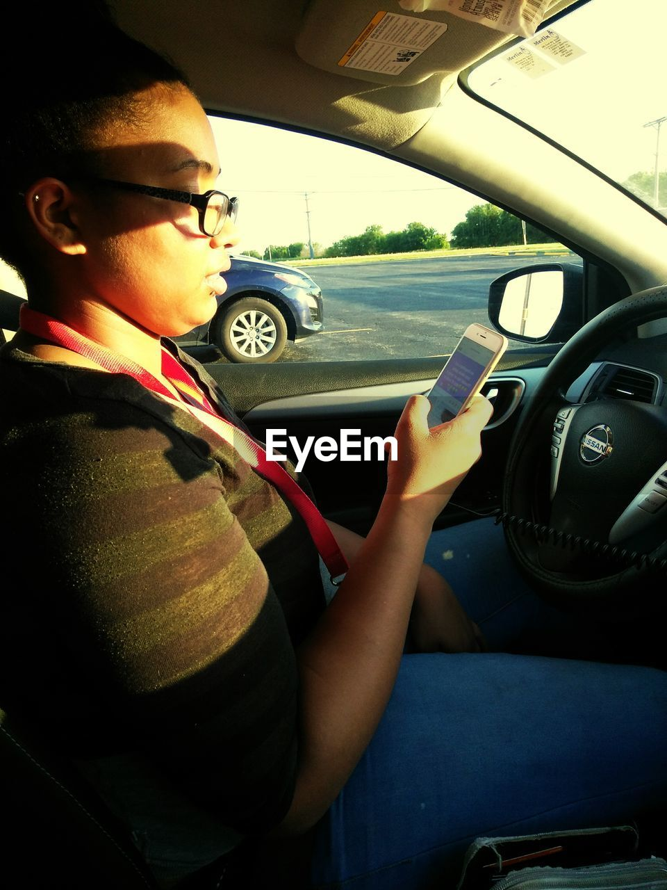 real people, car, transportation, one person, land vehicle, mode of transport, steering wheel, car interior, day, casual clothing, sitting, lifestyles, side view, stationary, cap, childhood, eyeglasses, road, outdoors
