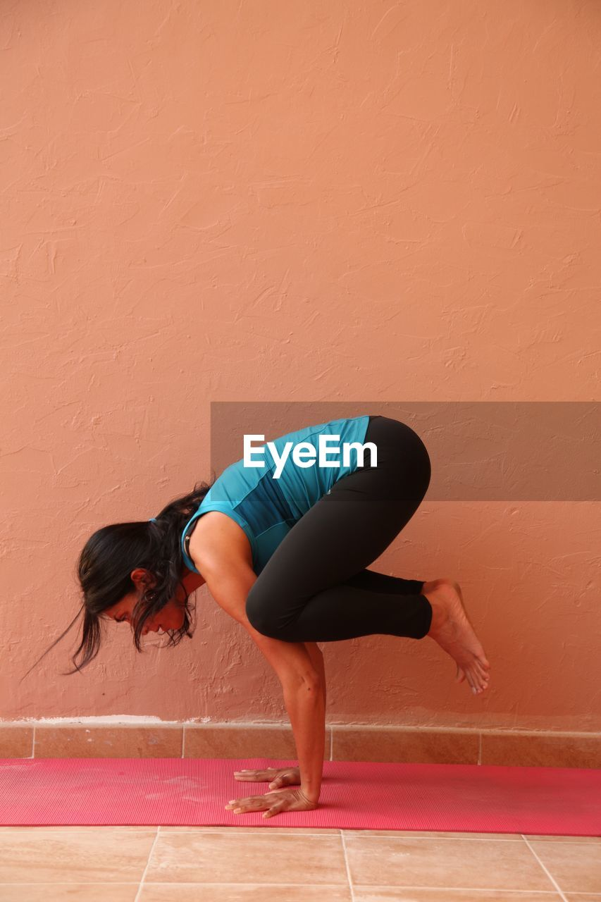 Young Woman In Crow Pose By Wall