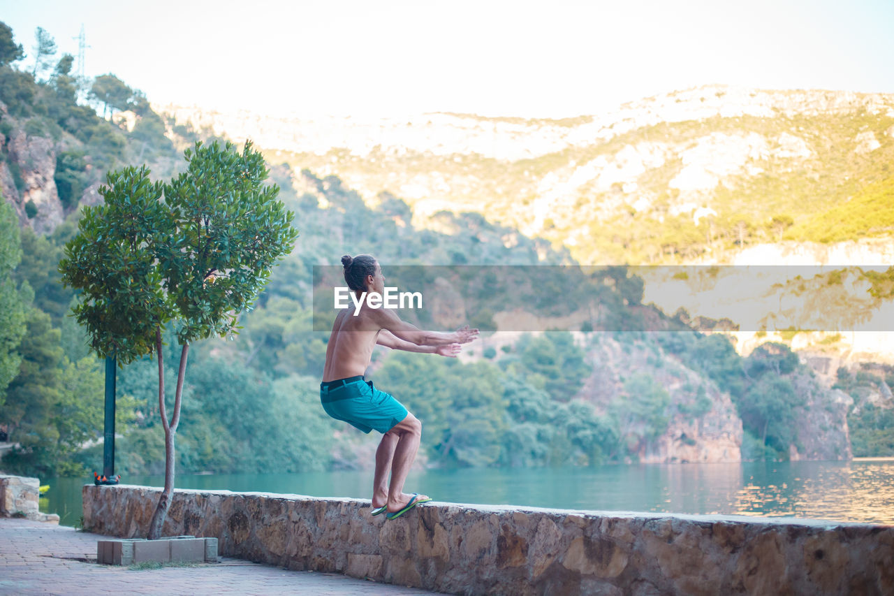 one person, shirtless, water, real people, lifestyles, nature, full length, men, tree, leisure activity, plant, day, motion, standing, beauty in nature, mountain, young adult, outdoors, shorts