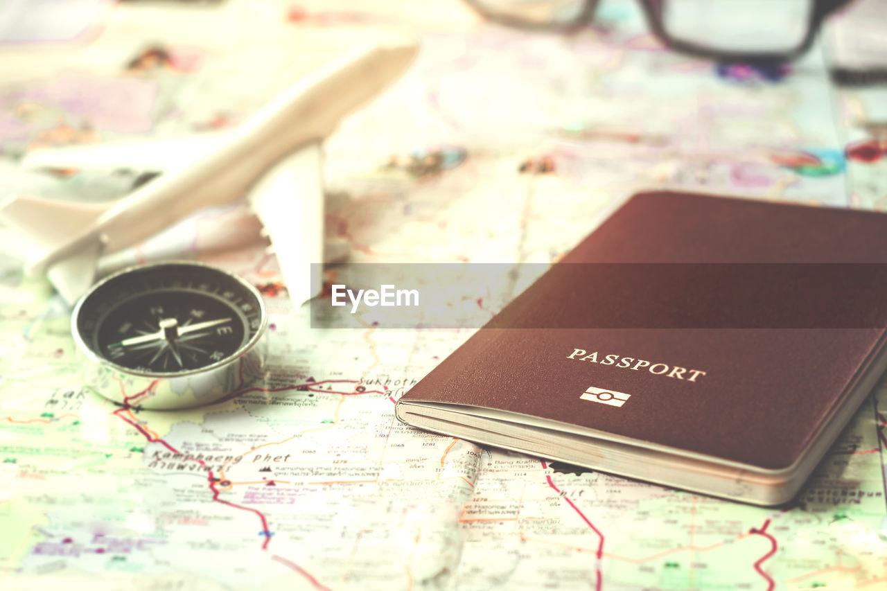 High angle view of navigational compass and passport on world map