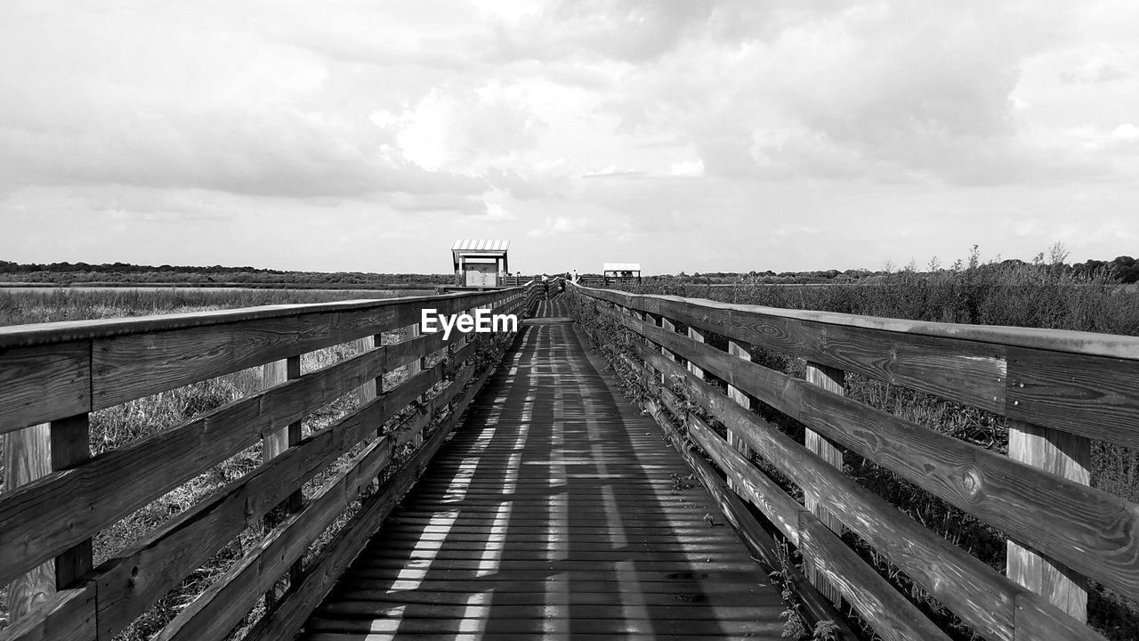 the way forward, sky, direction, cloud - sky, diminishing perspective, built structure, nature, day, connection, bridge, architecture, no people, transportation, vanishing point, railing, wood - material, outdoors, empty, bridge - man made structure, boardwalk, footbridge, long, wood paneling