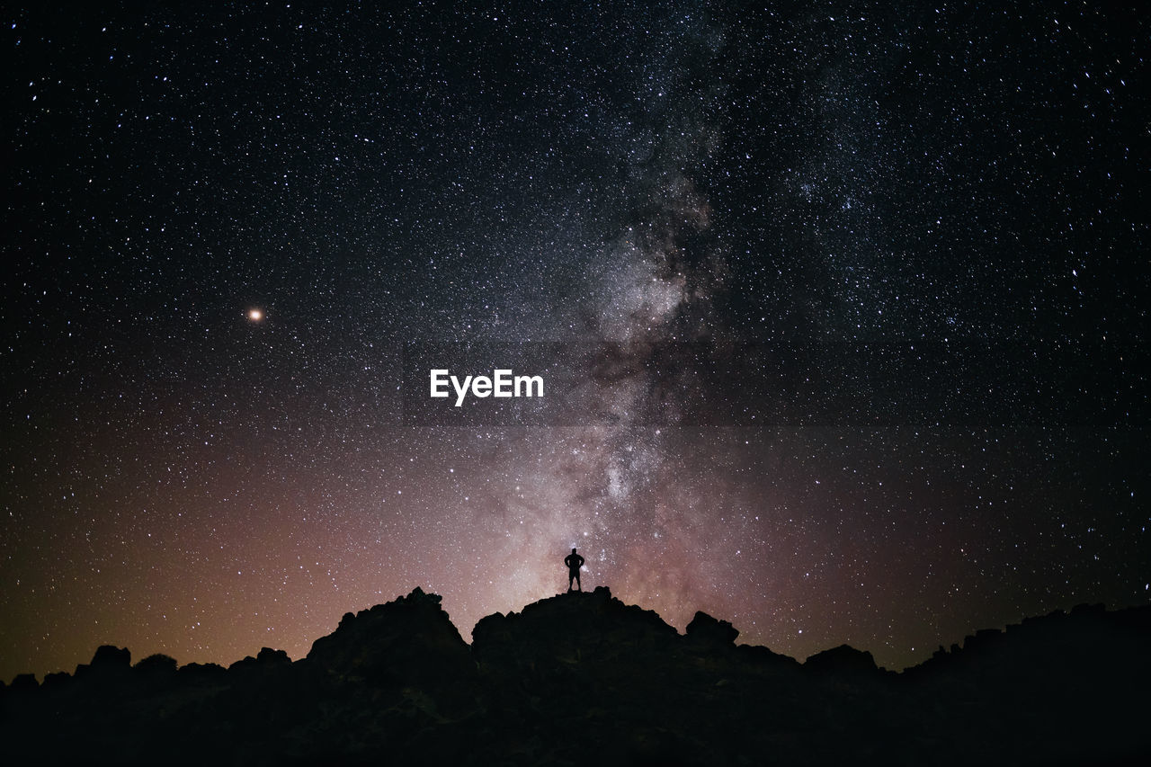 Silhouette Man Standing On Mountain Against Star Field At Night