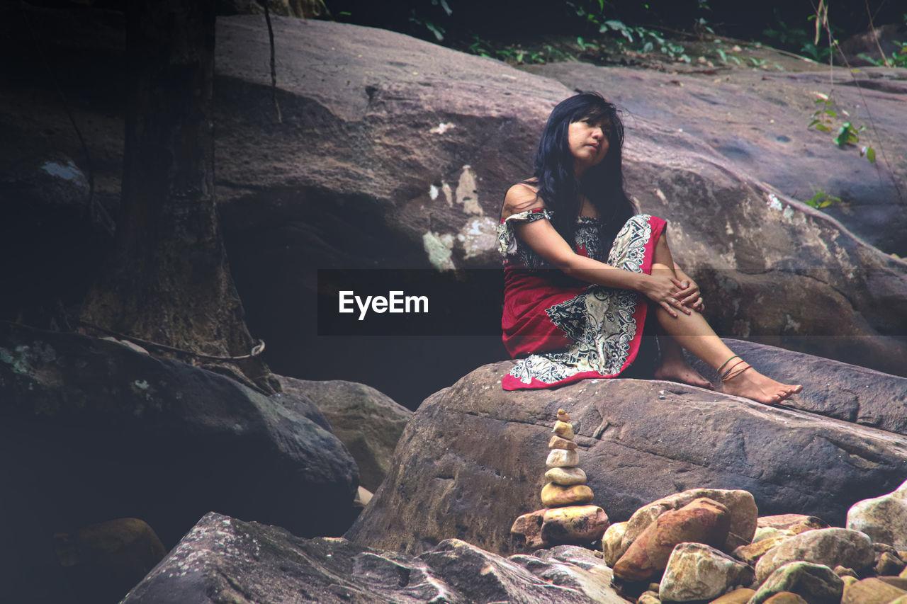 Thoughtful woman sitting on rock