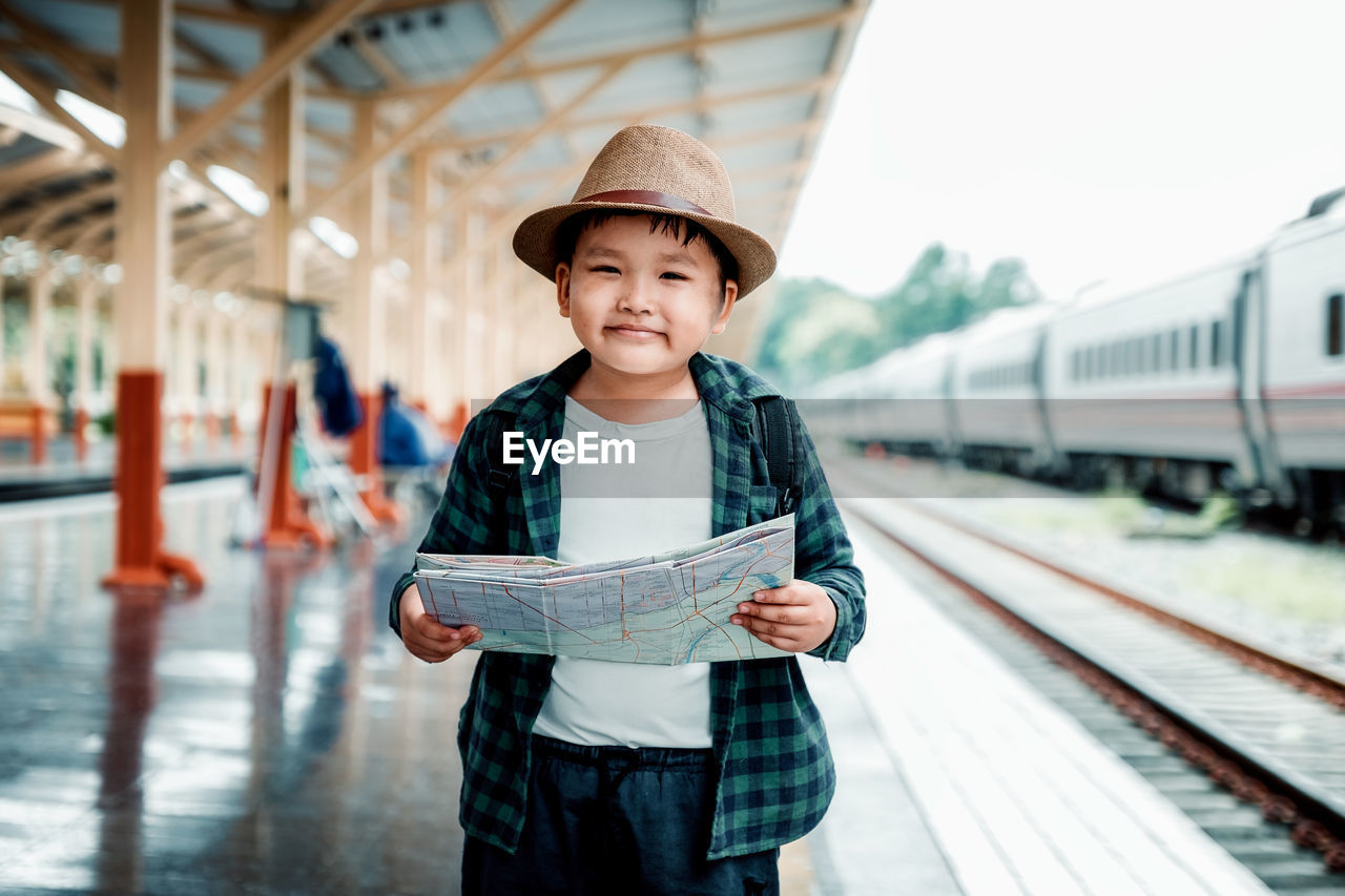 rail transportation, one person, childhood, front view, real people, males, boys, casual clothing, men, transportation, standing, train, train - vehicle, mode of transportation, child, looking at camera, public transportation, portrait, lifestyles, track, innocence