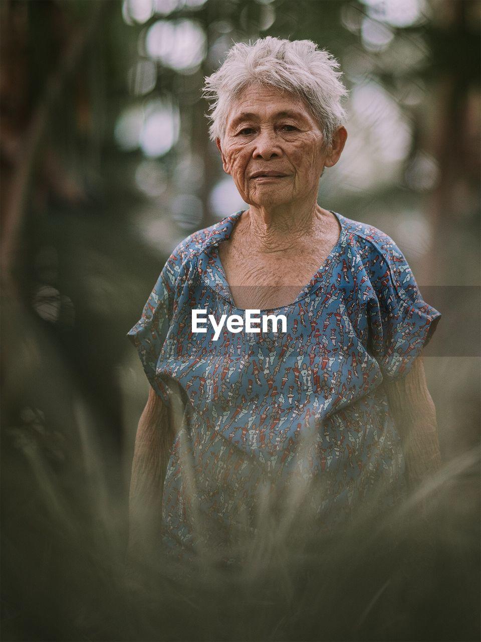 Portrait Of Senior Woman Seen Through Plants