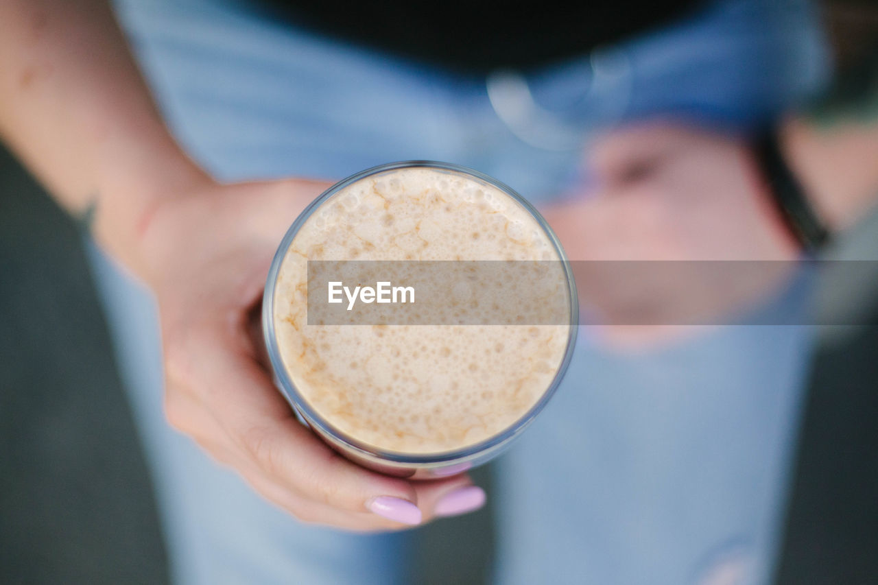 Close-up of hand holding  cold coffee glass