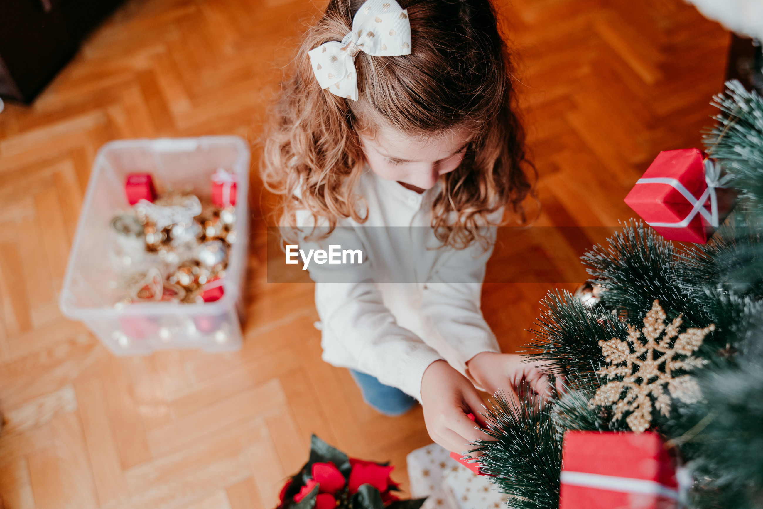 High angle view of cute girl decorating christmas tree at home