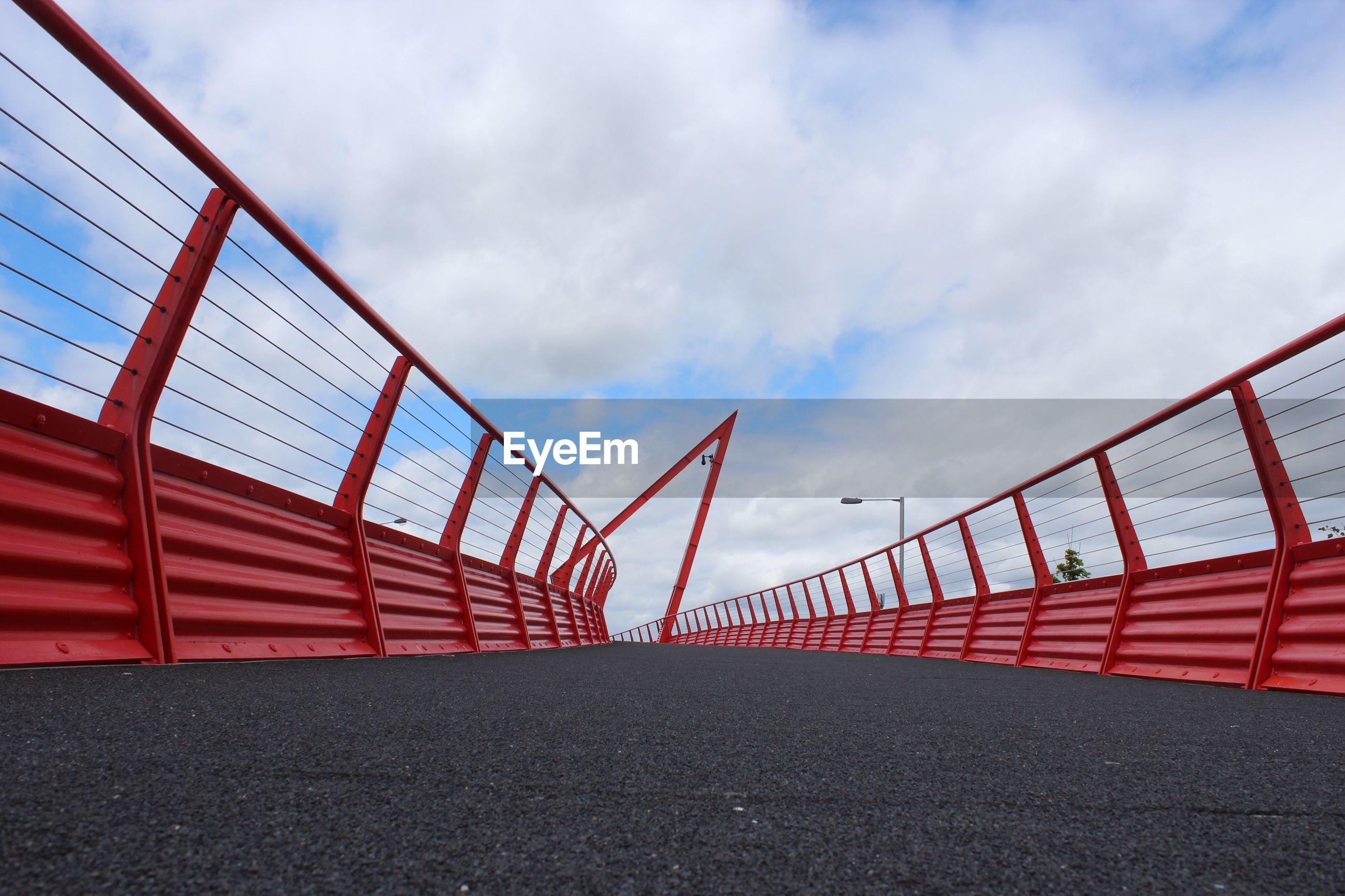 Red bridge against cloudy sky