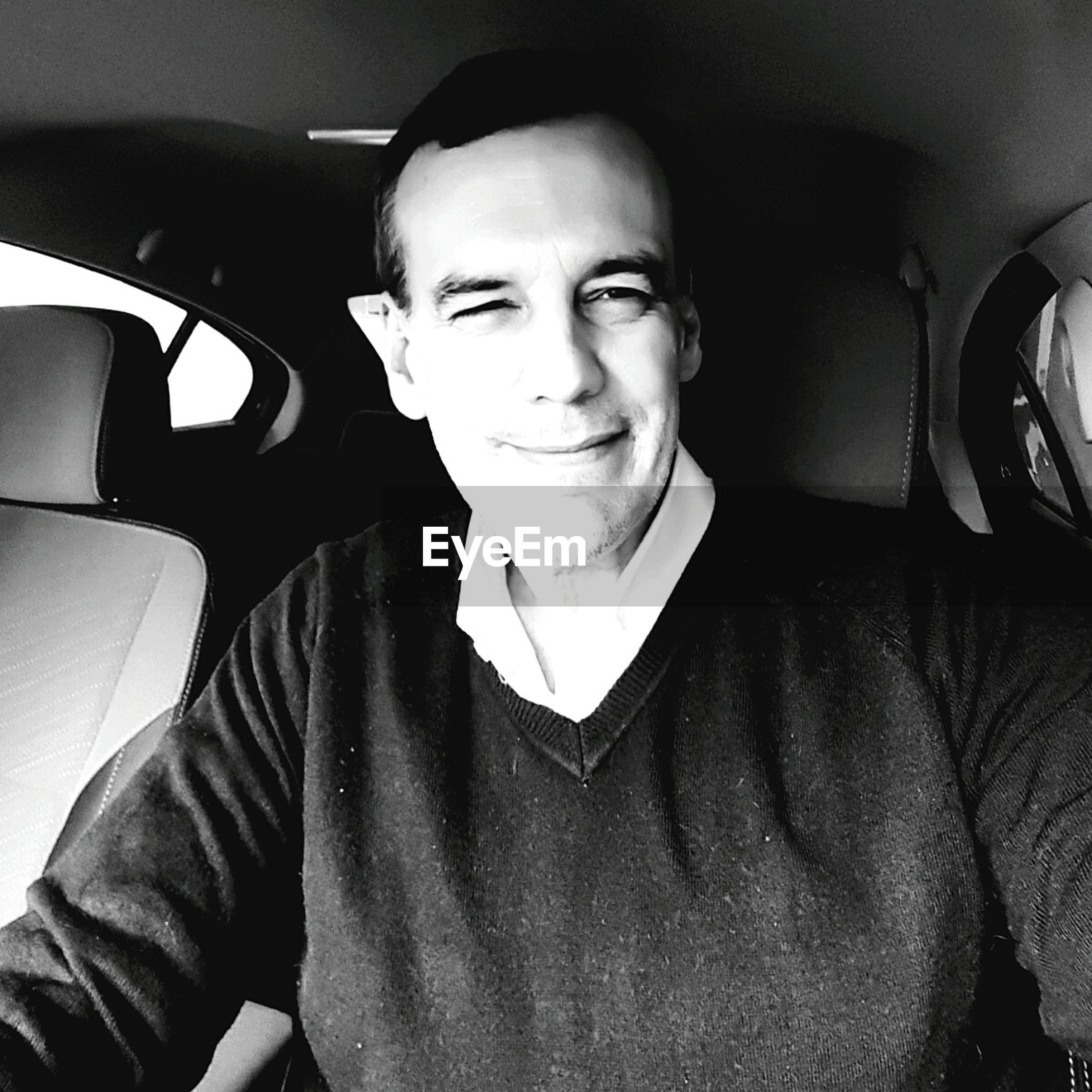 Smiling man wearing sweater sitting in car