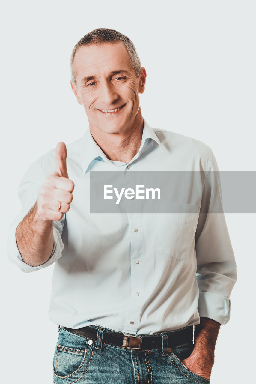 Portrait of smiling man showing thumbs up sign against white background