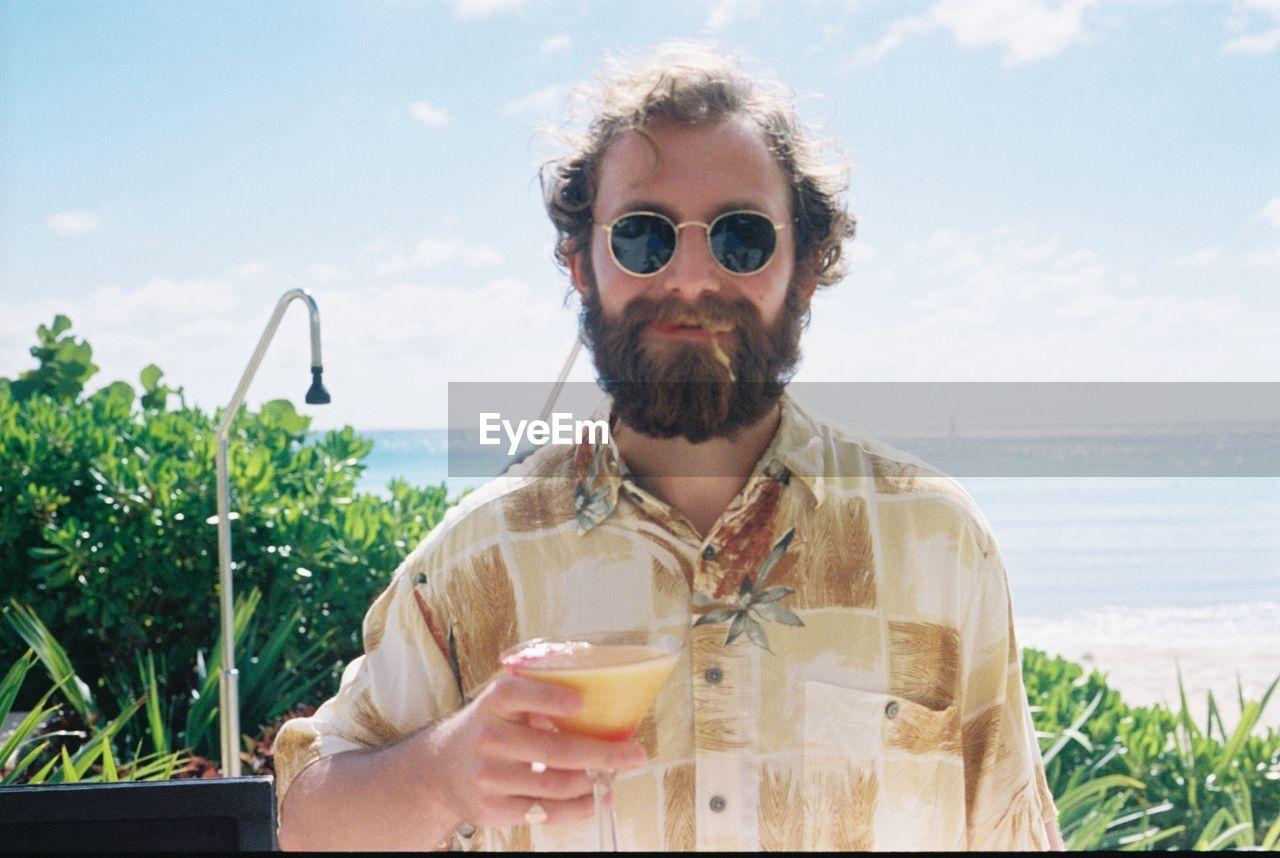 Portrait of man drinking cocktail in domestic garden
