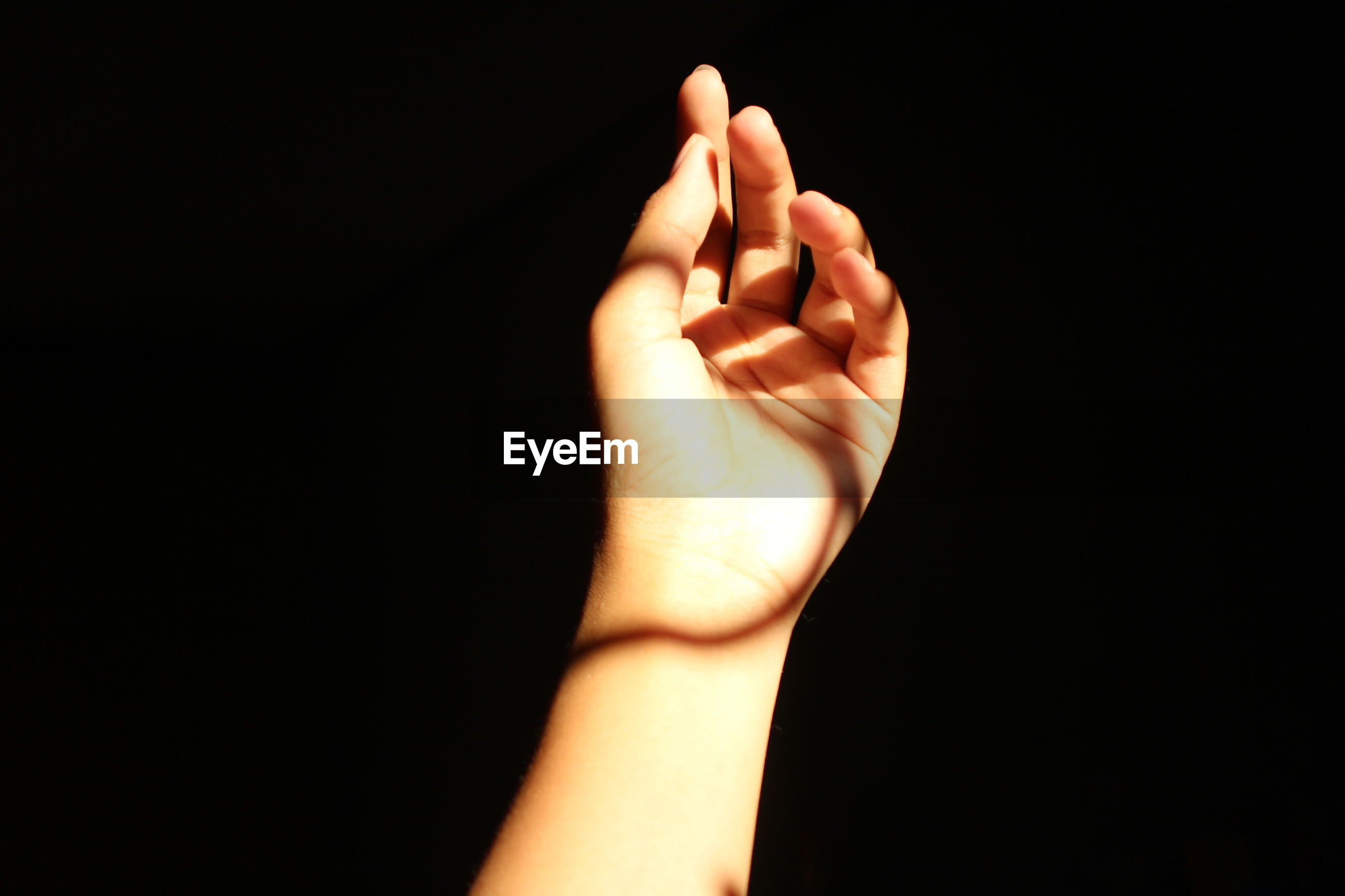 CROPPED IMAGE OF PERSON HAND WITH TEXT AGAINST BLACK BACKGROUND