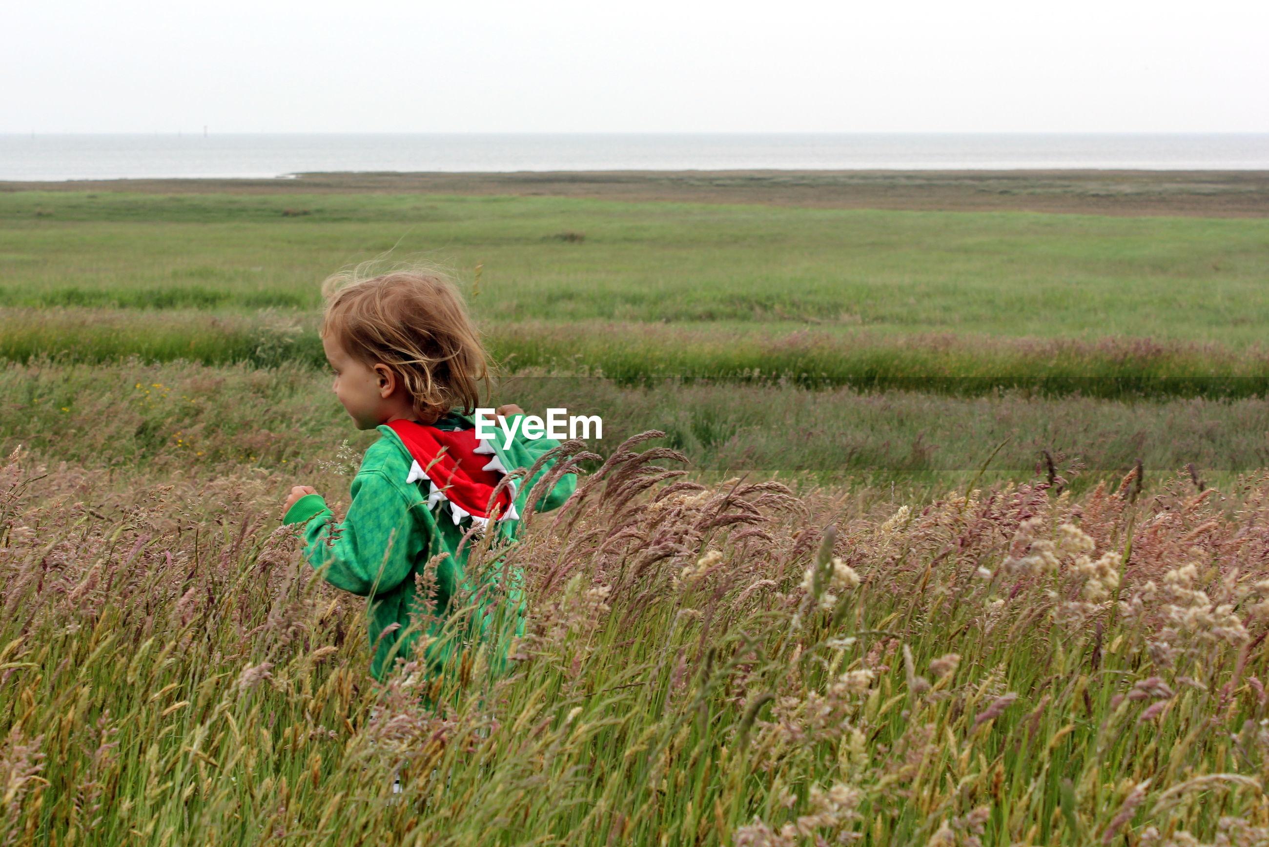 Girl on field against sky
