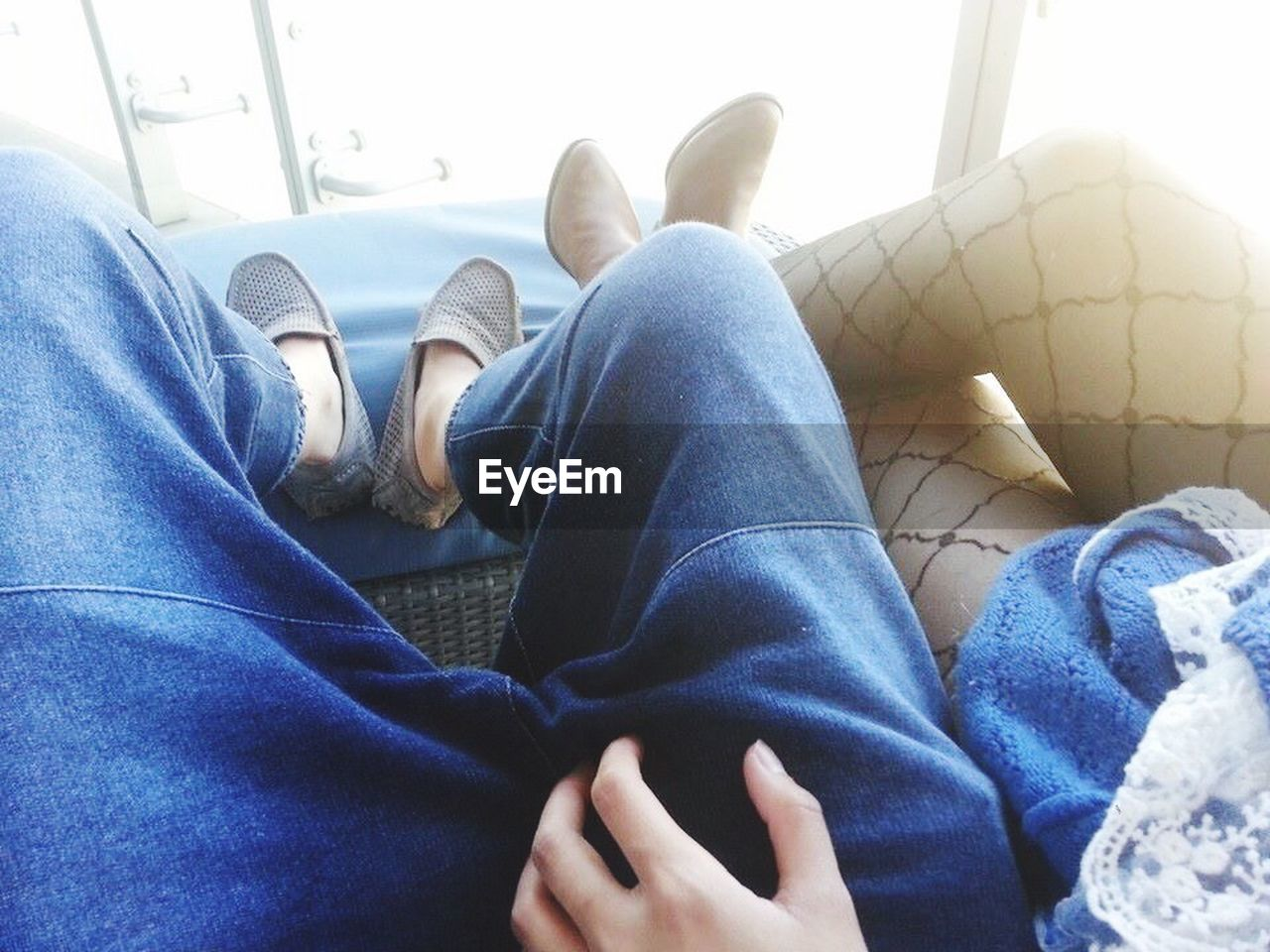 low section, human leg, jeans, relaxation, human foot, real people, barefoot, human body part, shoe, indoors, comfortable, lying down, sitting, casual clothing, resting, sofa, home interior, men, day, lifestyles, blue, close-up, human hand, adult, people