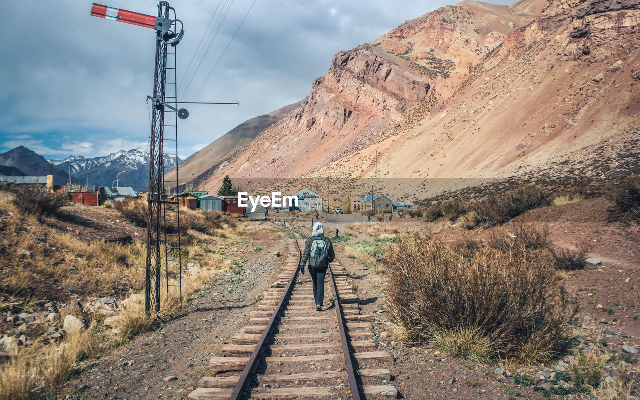 Person Walking On Railroad Track Against Mountain