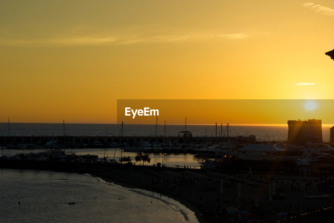 sunset, orange color, sea, sun, sky, water, no people, outdoors, city, architecture, cityscape, silhouette, nature, beauty in nature, building exterior, beach, built structure, nautical vessel, scenics, harbor, horizon over water