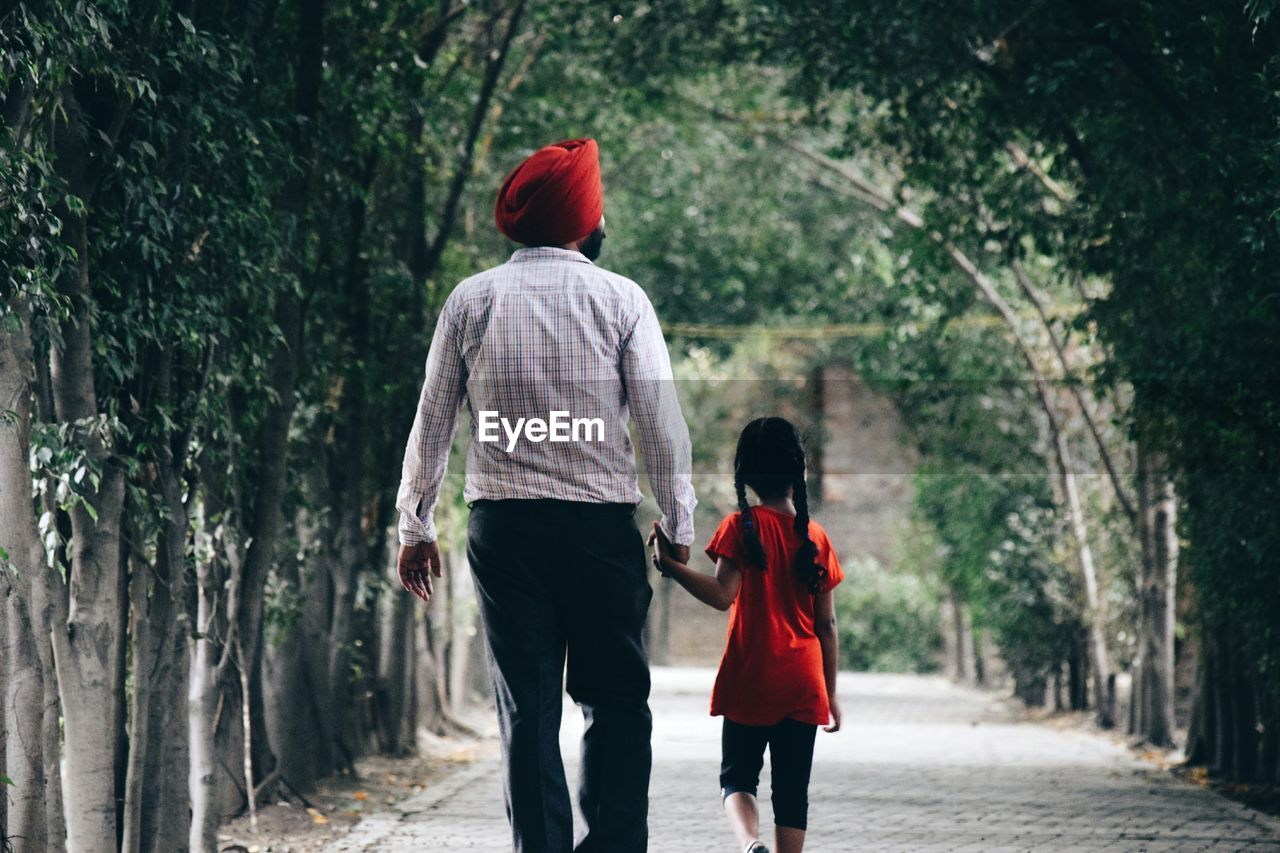 Rear View Of Father And Daughter Holding Hands