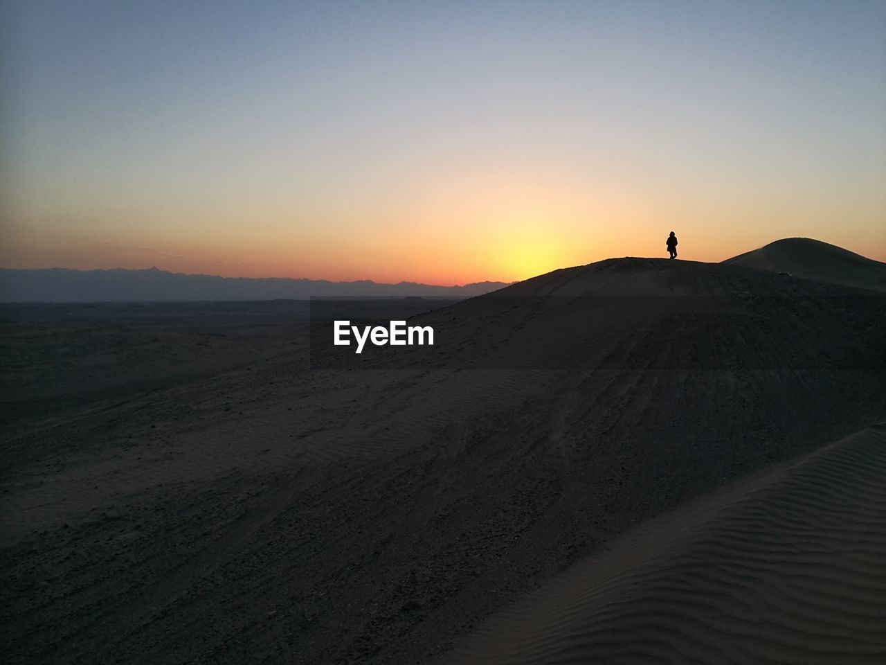 sky, sunset, scenics - nature, land, beauty in nature, tranquility, tranquil scene, environment, landscape, non-urban scene, real people, sand, nature, clear sky, desert, one person, copy space, silhouette, sand dune, mountain, arid climate, outdoors, climate