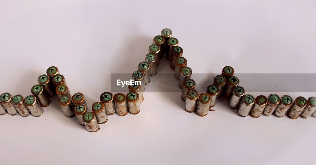 High Angle View Of Bullets Arranged In Pulse Trace At Table