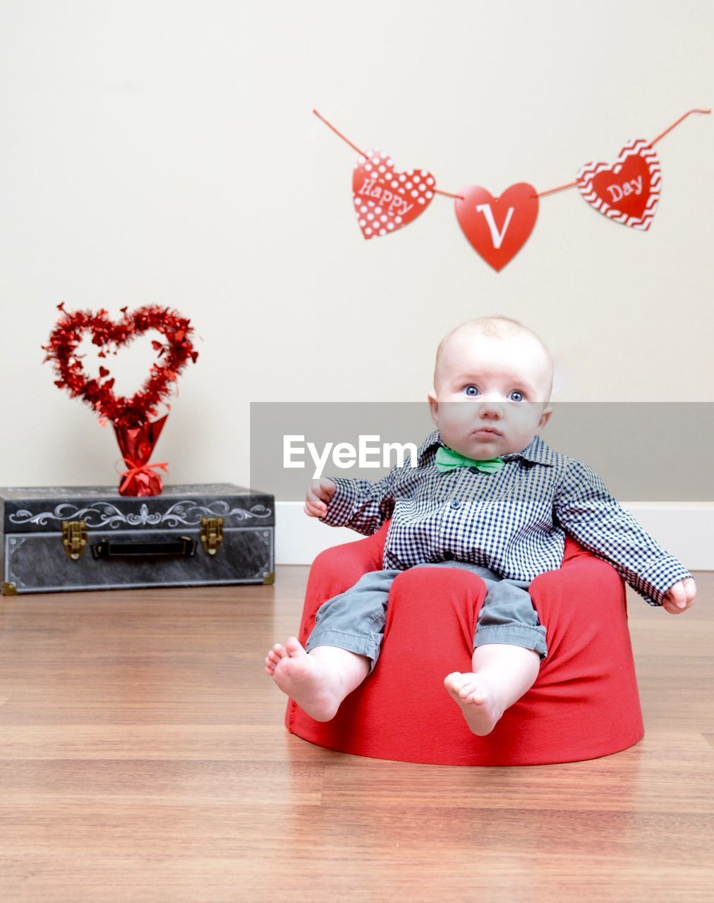 Toddler wearing bow tie sitting on floor seat at home during valentine day