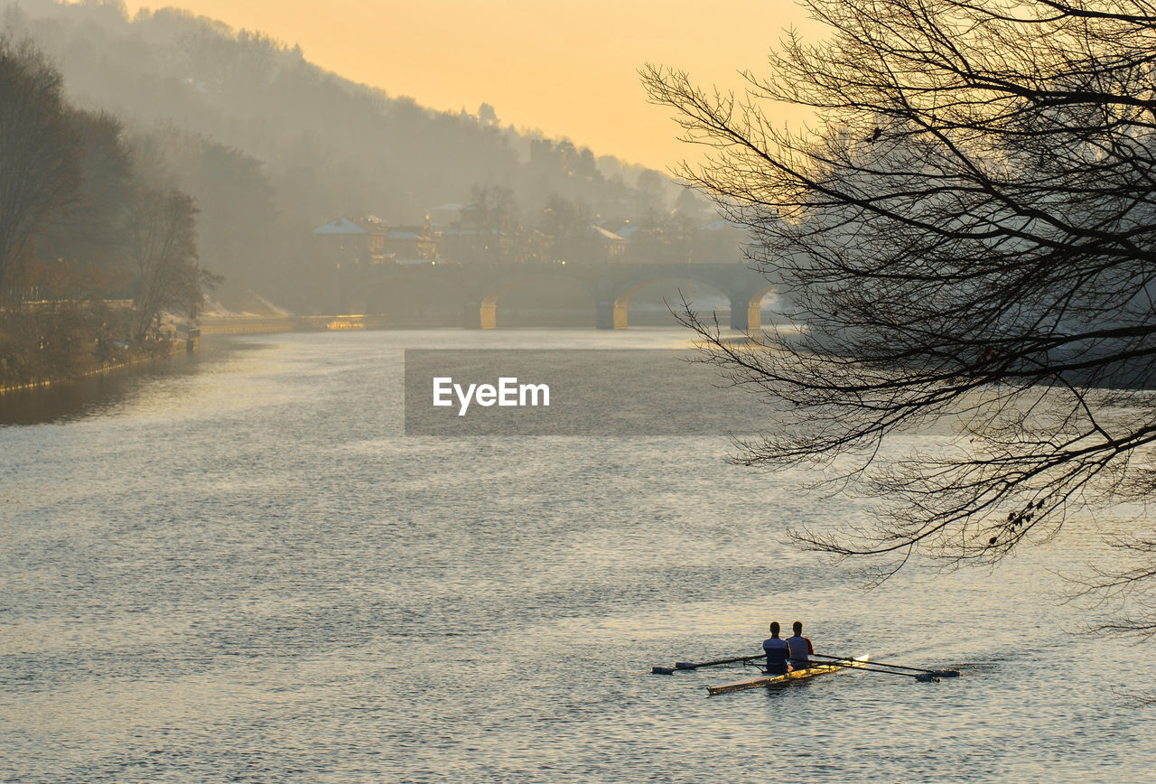 nautical vessel, transportation, mode of transportation, tree, water, real people, nature, plant, beauty in nature, waterfront, men, sky, day, lifestyles, scenics - nature, river, tranquil scene, outdoors, unrecognizable person, rowing