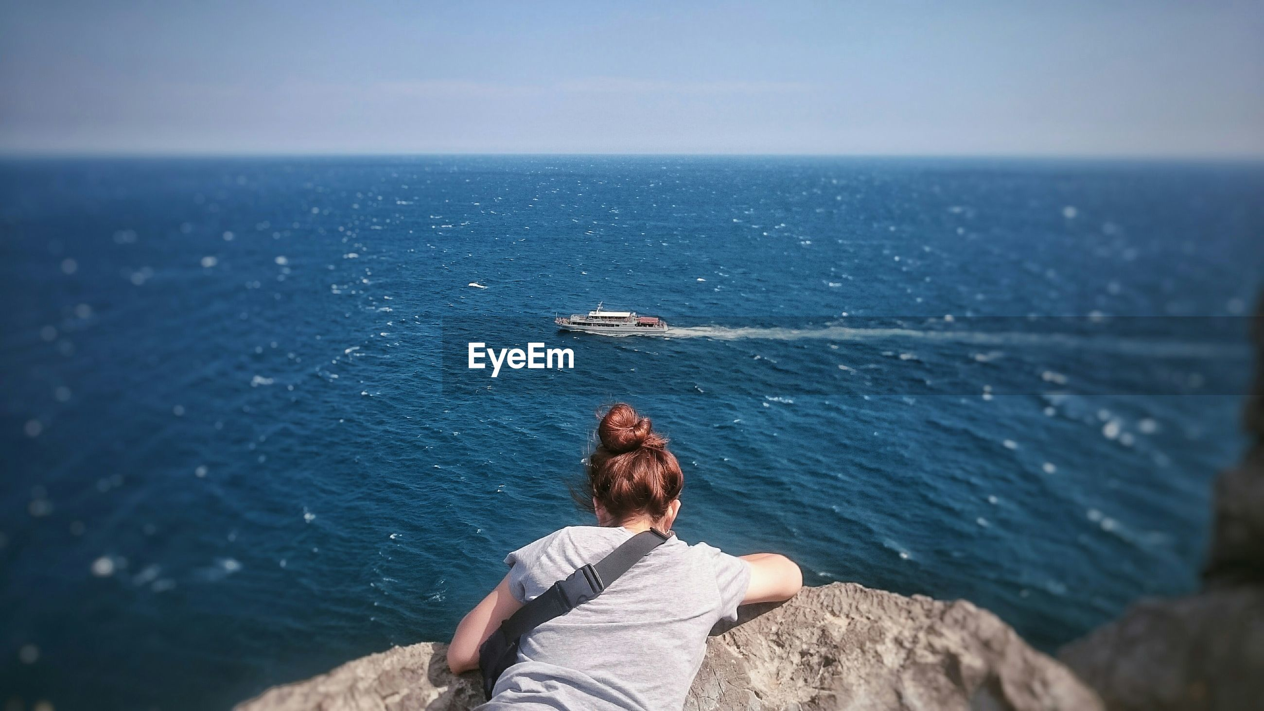 Rear view of woman lying on rock at seaside