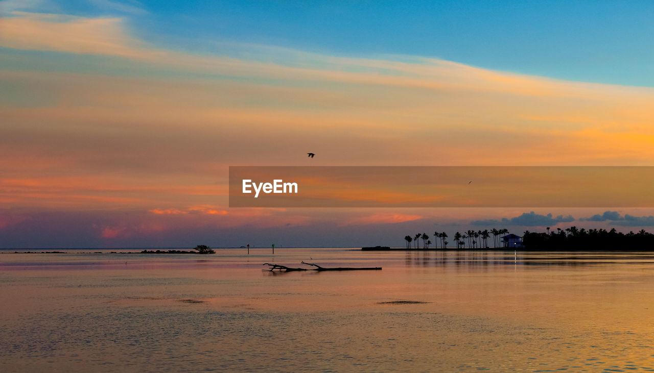 sky, sunset, scenics - nature, beauty in nature, water, cloud - sky, orange color, sea, tranquil scene, tranquility, nature, transportation, idyllic, beach, flying, land, air vehicle, horizon over water, mode of transportation, no people, outdoors
