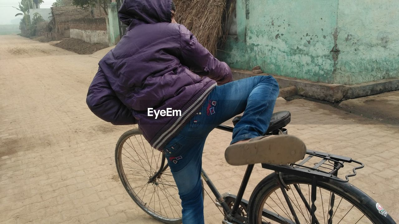 real people, bicycle, transportation, one person, mode of transport, day, casual clothing, rear view, outdoors, land vehicle, lifestyles, sitting, full length, architecture, people