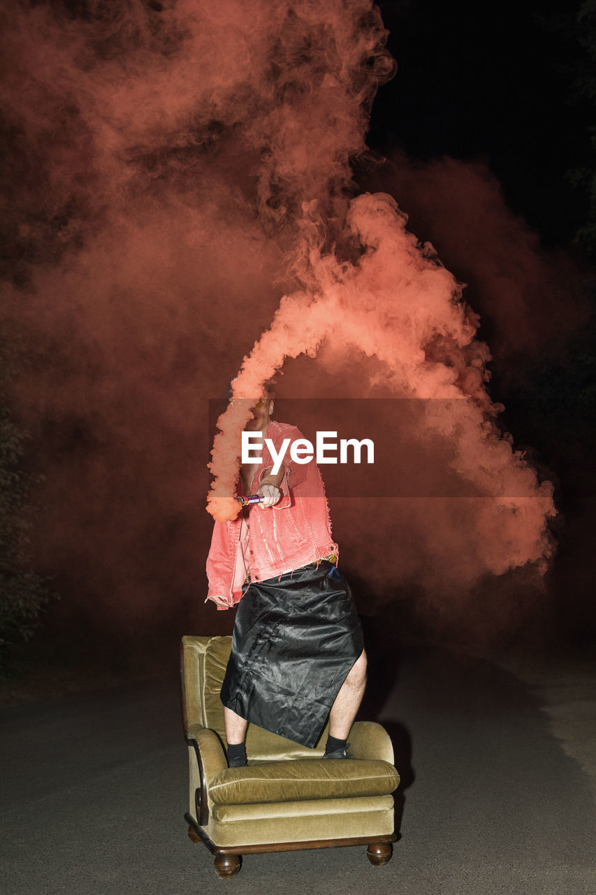 one person, smoke - physical structure, real people, full length, casual clothing, motion, holding, men, rear view, burning, fire, heat - temperature, flame, nature, fire - natural phenomenon, standing, outdoors, lifestyles, day