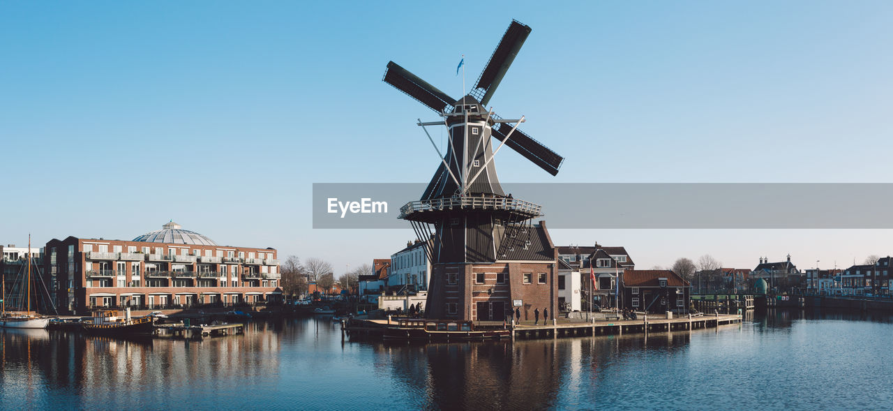 architecture, building exterior, alternative energy, built structure, windmill, wind power, renewable energy, waterfront, wind turbine, no people, water, clear sky, day, outdoors, traditional windmill, blue, travel destinations, nautical vessel, sky, nature, city, industrial windmill