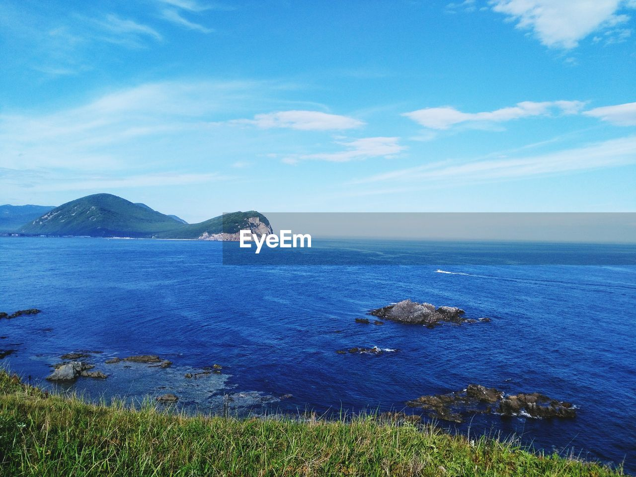 sea, water, scenics - nature, sky, beauty in nature, tranquil scene, tranquility, cloud - sky, nature, horizon, blue, land, horizon over water, no people, idyllic, day, grass, non-urban scene, mountain, stack rock