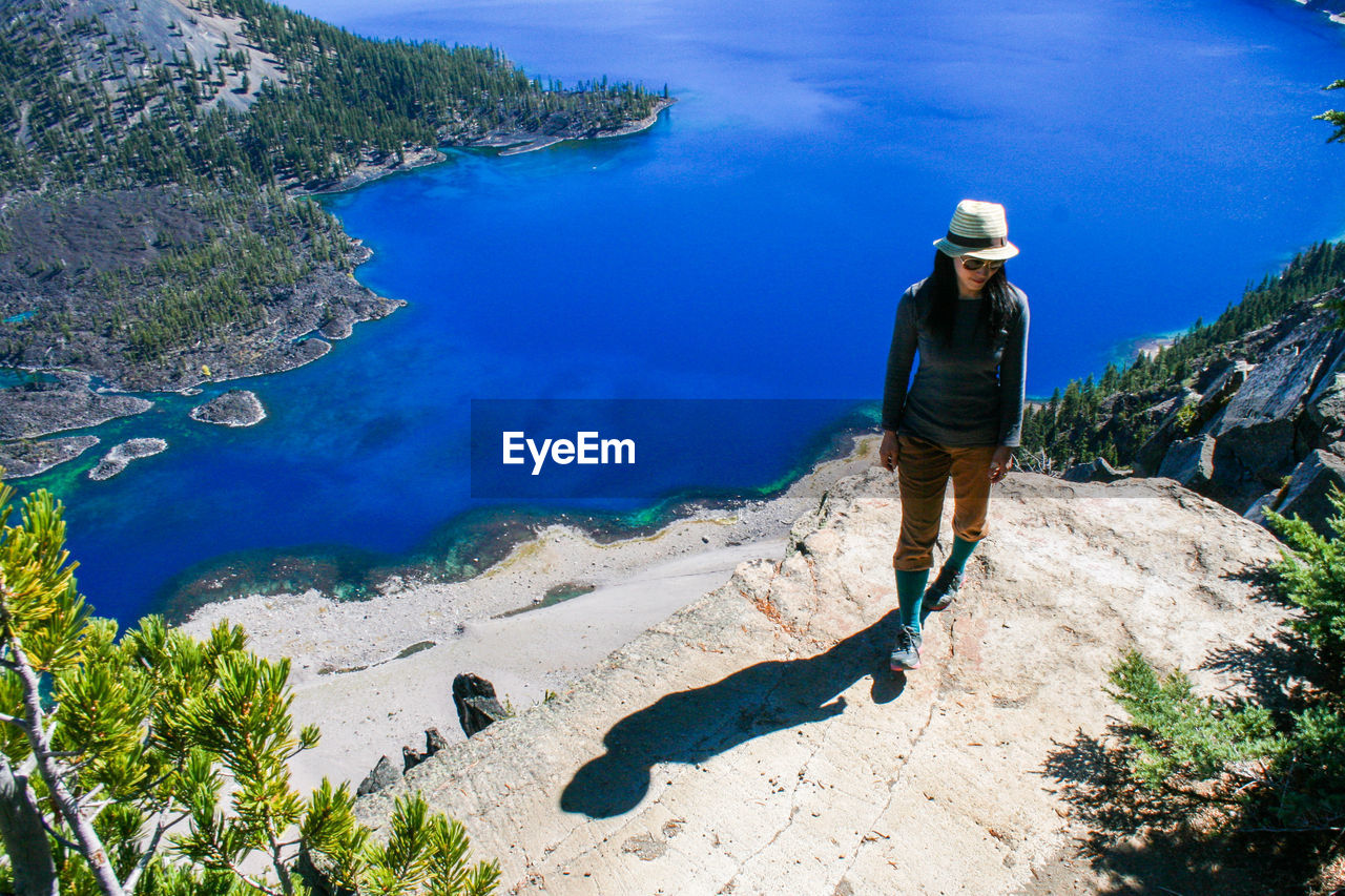 High Angle View Of Young Woman Standing On Cliff By Crater Lake