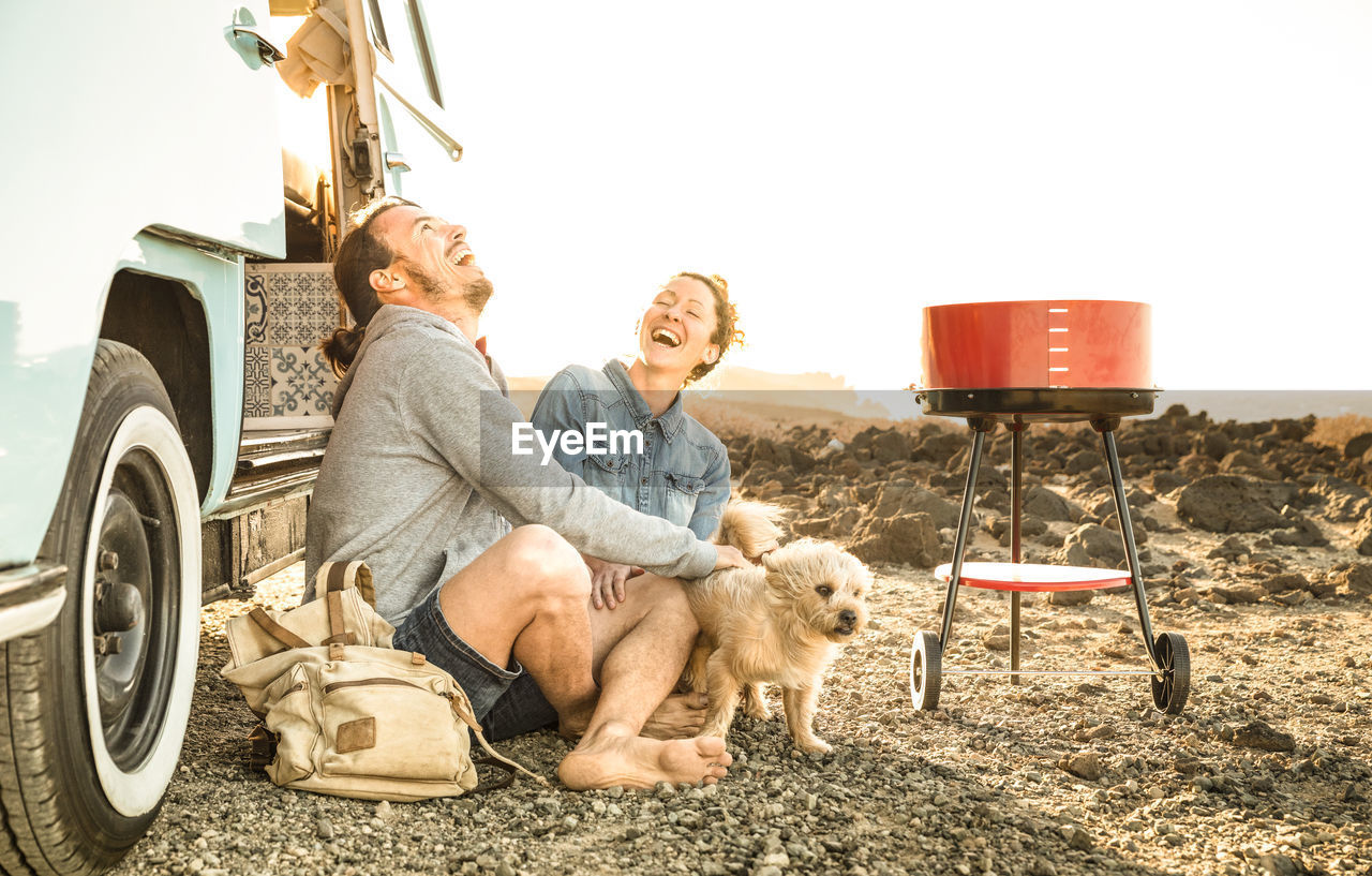 Happy Couple With Dog Sitting On Field
