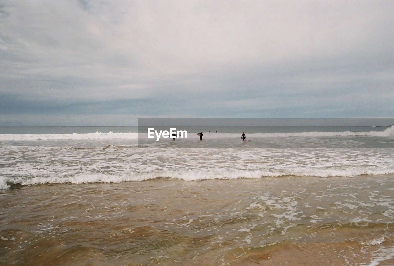 sea, water, nature, beach, real people, sky, horizon over water, leisure activity, beauty in nature, scenics, wave, outdoors, sport, two people, cloud - sky, tranquility, lifestyles, men, skill, day, extreme sports, people