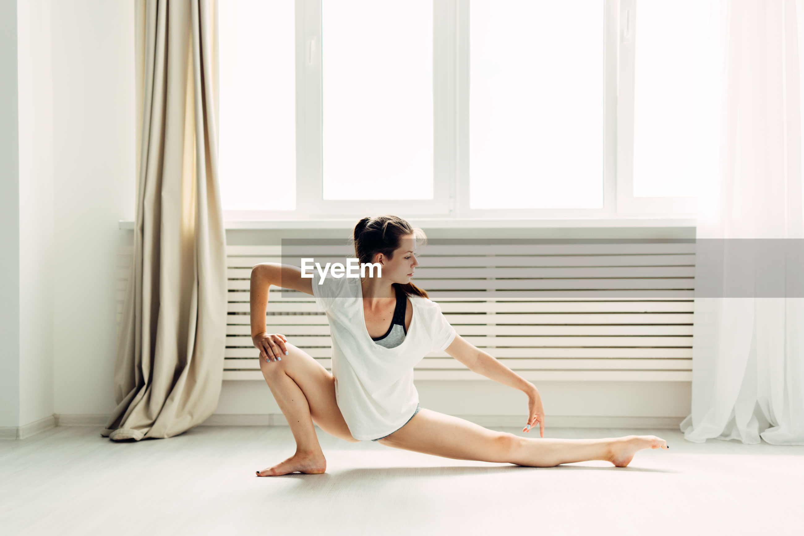 Full length of young woman stretching legs while practicing yoga at home