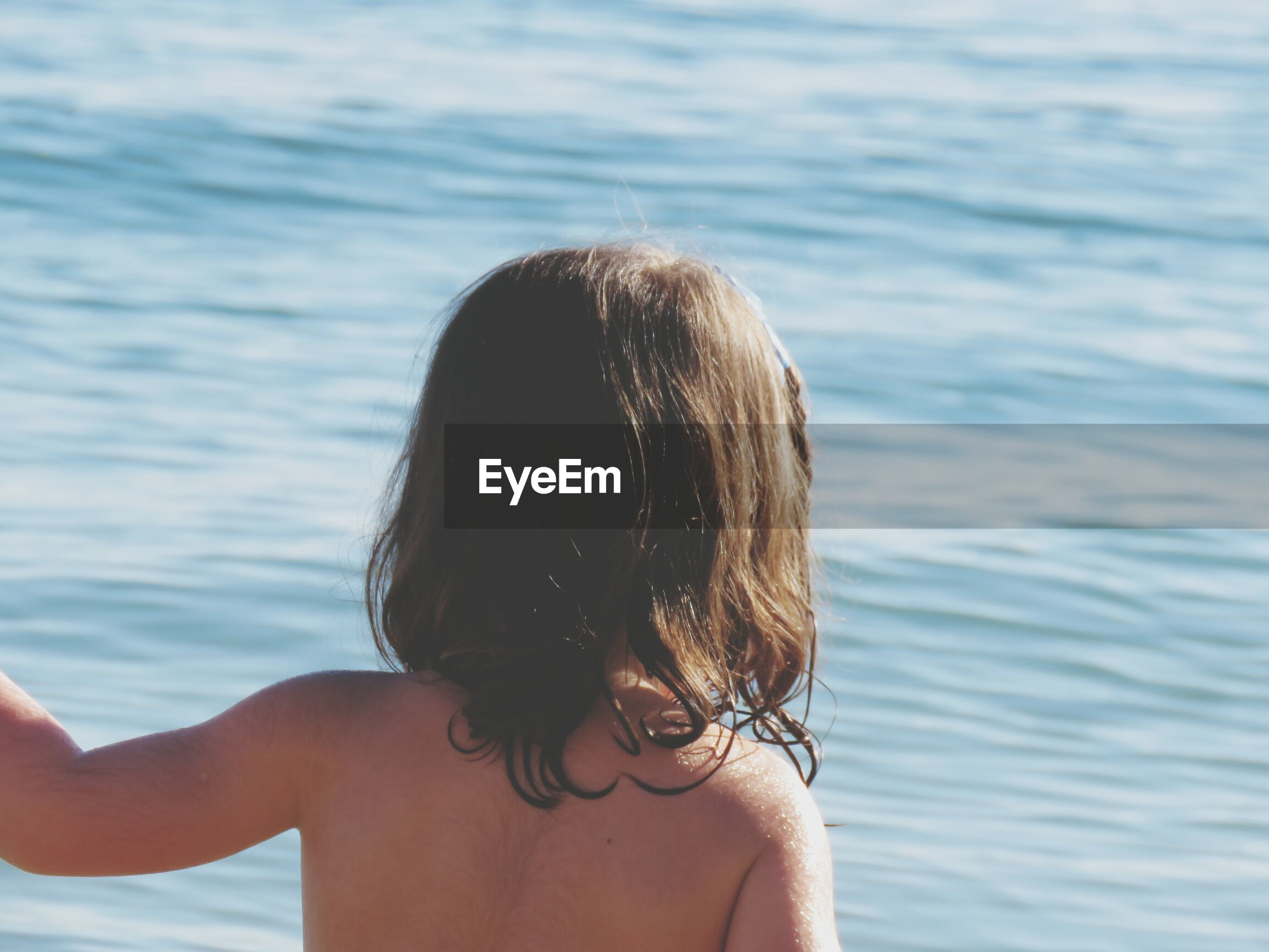 Rear view of topless girl against sea