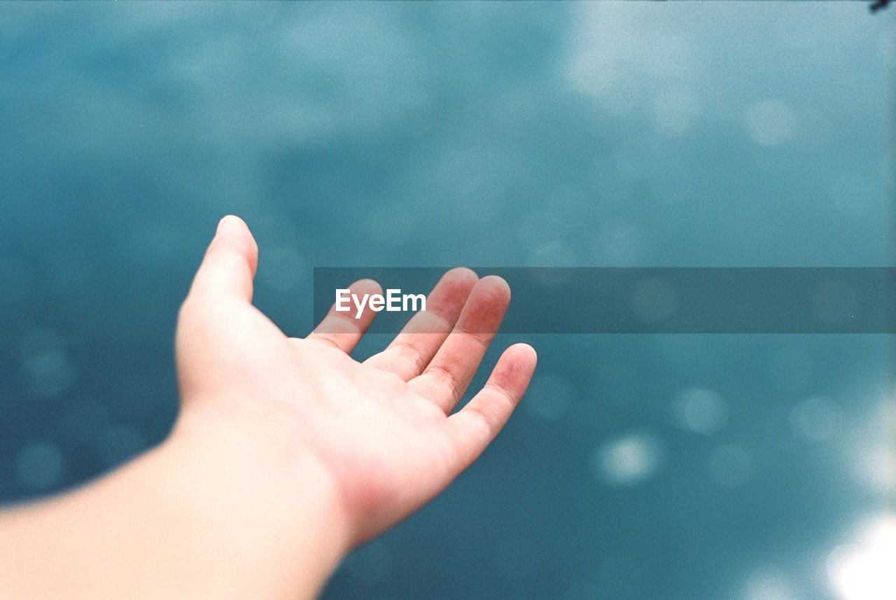 Cropped Image Of Hand Against Sea