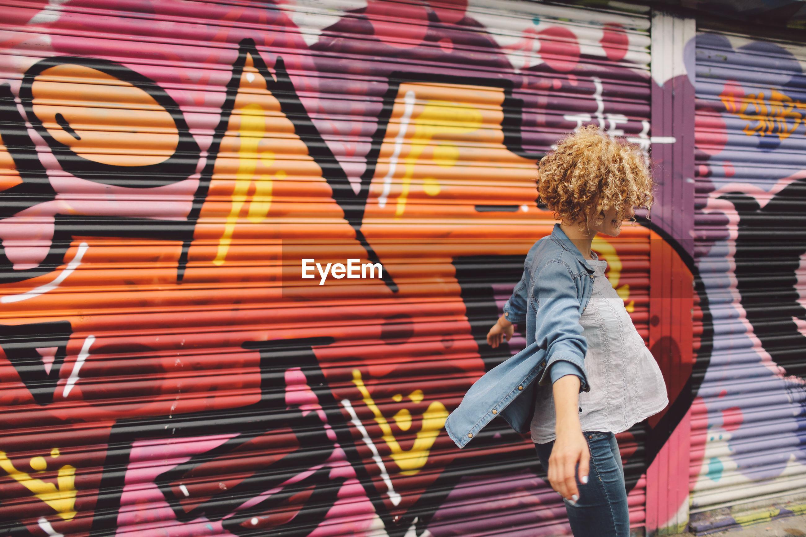 Young woman dancing against graffiti shutter