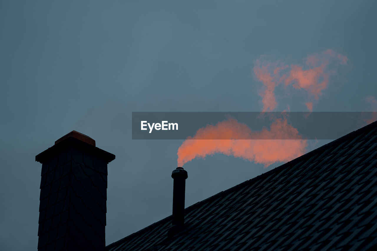 Low angle view of smoke emitting from chimney against sky at sunset