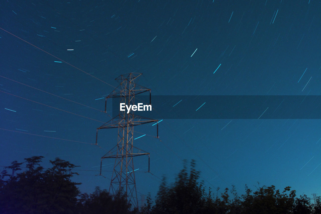 LOW ANGLE VIEW OF ELECTRICITY PYLON AGAINST STAR FIELD