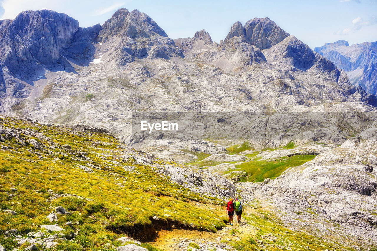Rear view of hikers walking on mountain against sky