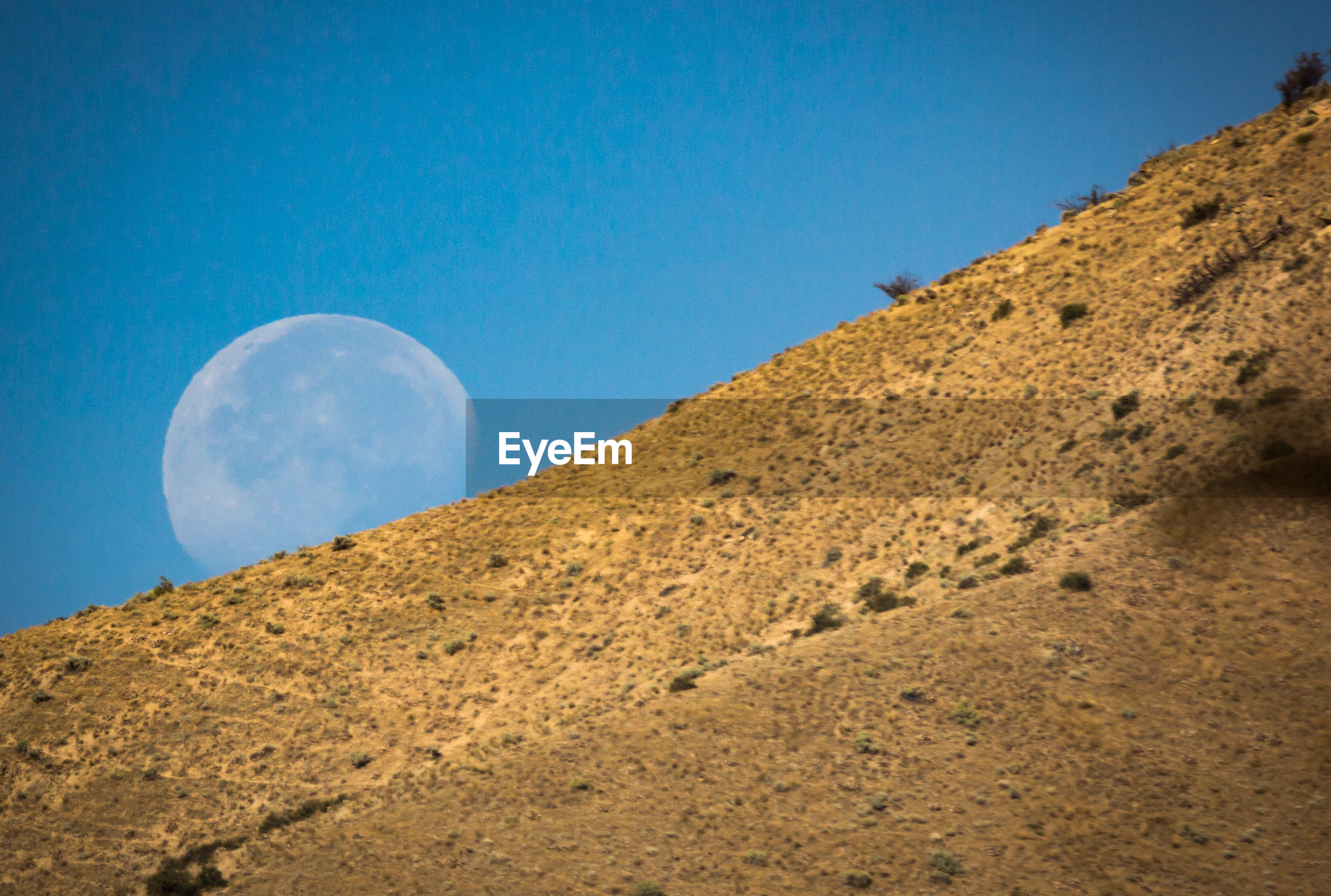 Moon rising behind a mountain