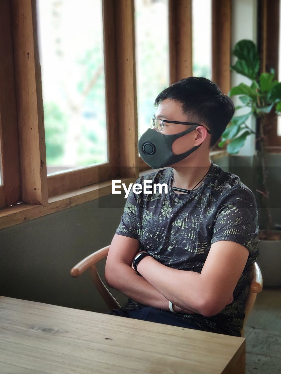 Man wearing mask while sitting on table at restaurant