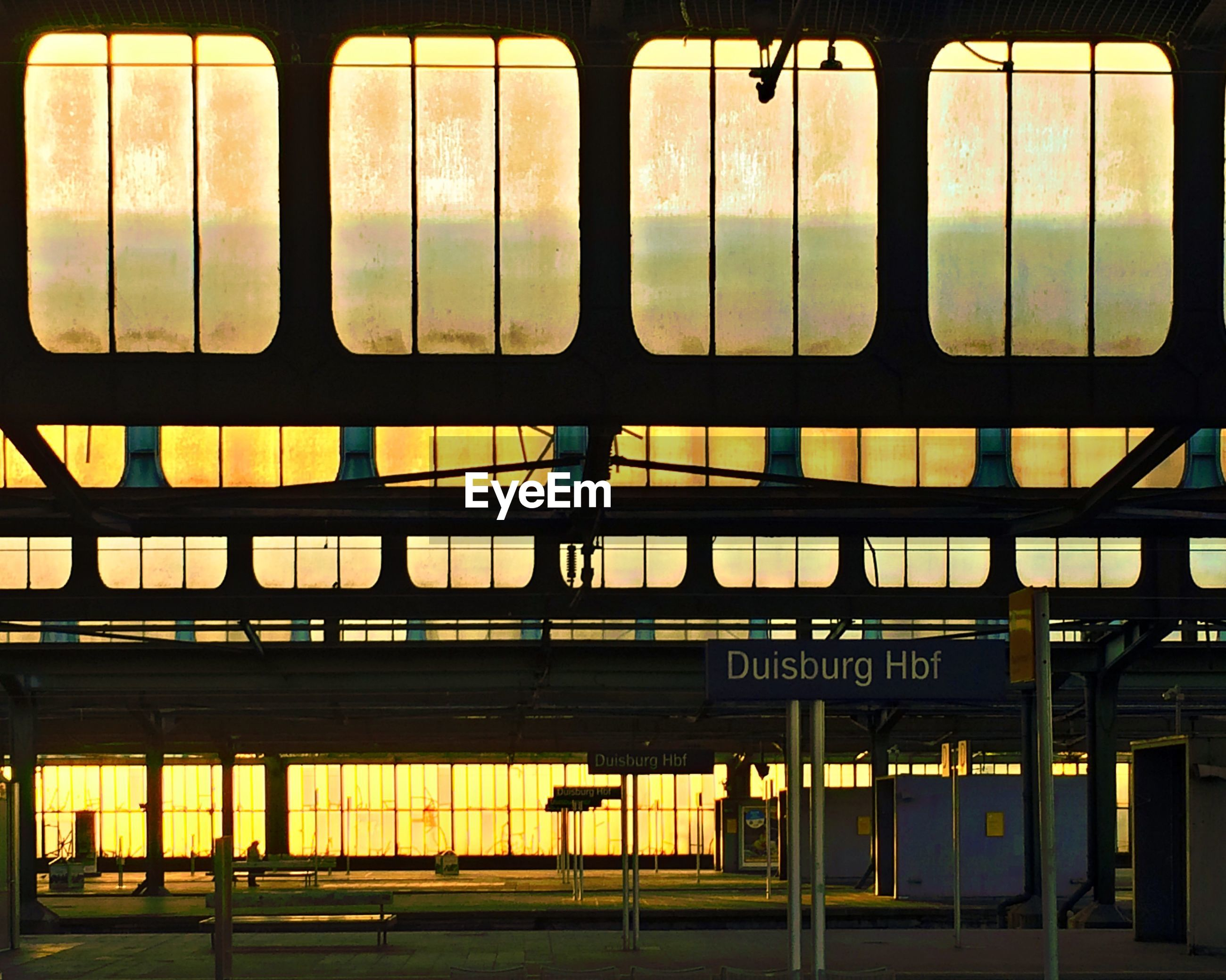 sunset, yellow, architecture, window, built structure, orange color, indoors, railroad station, public transportation, illuminated, transportation, rail transportation, sky, no people, railing, glass - material, text, building exterior, railroad station platform, fence